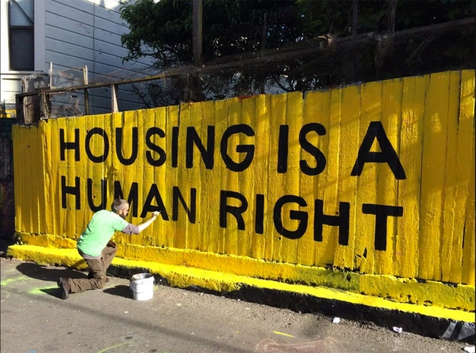 Man painting fence that says housing is a human right.